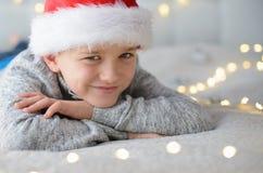 愉快的微笑的孩子在床上的圣诞老人帽子在圣诞节 库存图片