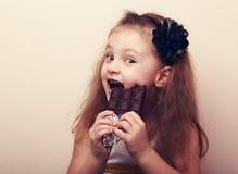 愉快的微笑的孩子女孩尖酸的鲜美巧克力 黑色图象纵向葡萄酒白色 免版税库存照片