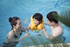 愉快的微笑的家庭教的儿子如何游泳在水池 免版税库存图片