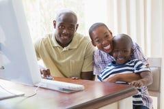 愉快的微笑的家庭画象使用计算机的 免版税库存照片