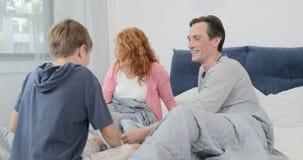 愉快的微笑的家庭n卧室一起,跳跃在床上的儿子在早晨 股票录像