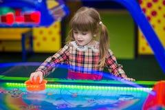愉快的微笑的小女孩戏剧空气曲棍球 免版税库存图片