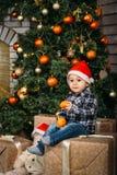 愉快的微笑的小男孩圣诞节画象红色圣诞老人帽子的坐有礼物的箱子在手上的拿着桔子 免版税图库摄影