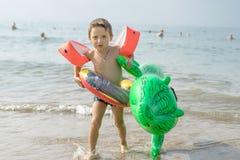 愉快的微笑的小男孩跑与波浪的戏剧在海滩 意大利 夏天 免版税库存照片