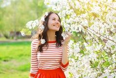 愉快的微笑的少妇在开花的春天庭院里 库存图片