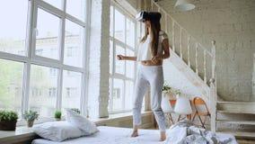 愉快的微笑的少妇跳舞,当得到经验使用虚拟现实360块VR耳机玻璃在床上的在时 免版税库存照片