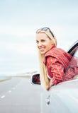 愉快的微笑的少妇从车窗看  免版税库存图片