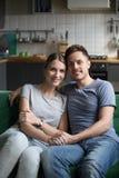 愉快的微笑的年轻夫妇,家庭垂直的画象  免版税库存照片