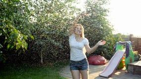 愉快的微笑的年轻女人慢动作英尺长度跳舞和跳跃在温暖的夏天雨下的白色T恤的在日落 股票录像