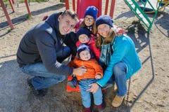 愉快的微笑的幼小五口之家在儿童` s操场在公园 库存照片