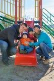 愉快的微笑的幼小四口之家在儿童` s操场在公园 免版税库存照片