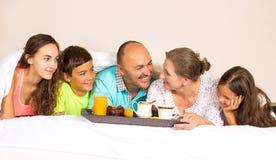 愉快的微笑的快乐的家庭吃早餐在床 免版税库存图片