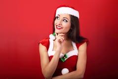 愉快的微笑的想法的妇女在圣诞老人圣诞节服装lo 免版税库存图片