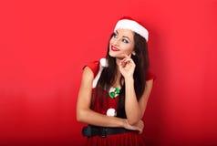 愉快的微笑的想法的妇女在圣诞老人圣诞节服装lo 库存图片