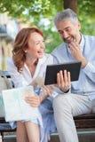 愉快的微笑的成熟游人坐看片剂和笑的长凳 免版税图库摄影