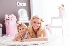 愉快的微笑的放置在一个地板的女儿和妈妈在他们的房子里 库存图片
