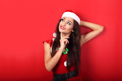 愉快的微笑的松弛妇女在圣诞老人圣诞节服装Th 免版税库存图片