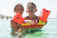 愉快的微笑的母亲和儿子画象海上,室外 Concep 图库摄影