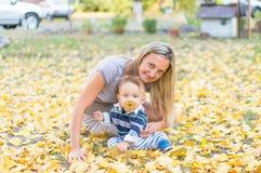 愉快的微笑的母亲和小使用与黄色叶子的男婴在公园 免版税库存照片