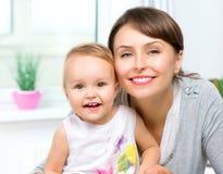 愉快的微笑的母亲和婴孩 免版税库存照片
