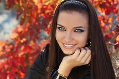愉快的微笑的深色的女孩。 秋天妇女 免版税库存照片