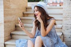 年轻愉快的微笑的深色的女孩听的音乐户外 库存图片
