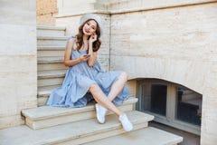 年轻愉快的微笑的深色的女孩听的音乐户外 免版税库存图片
