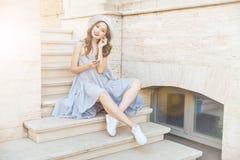 年轻愉快的微笑的深色的女孩听的音乐户外 库存照片