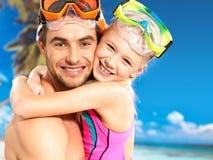 愉快的微笑的父亲拥抱女儿在热带海滩 免版税图库摄影