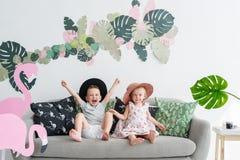 愉快的微笑的男孩和女孩使用在沙发的草帽的在屋子里 免版税库存图片