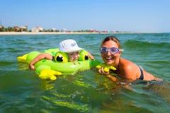 愉快的微笑的男孩在与一个年轻母亲的橡胶圆盘游泳  免版税库存照片