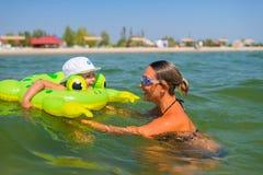愉快的微笑的男孩在与一个年轻母亲的橡胶圆盘游泳  免版税图库摄影