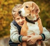 愉快的微笑的男孩拥抱他的最好的朋友小猎犬狗 免版税库存照片