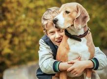 愉快的微笑的男孩拥抱他的最好的朋友小猎犬狗 免版税库存图片
