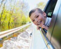 愉快的微笑的男孩看车窗 免版税图库摄影