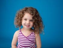 愉快的微笑的笑的孩子:有卷发的女孩 免版税库存图片