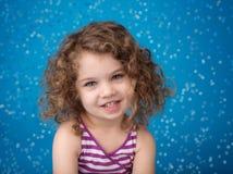 愉快的微笑的笑的孩子:蓝色背景冰冷的结冰的Snowfla 免版税图库摄影