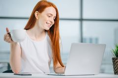 愉快的微笑的红头发人妇女与膝上型计算机和饮用的咖啡一起使用 库存图片