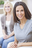 愉快的微笑的美丽的妇女坐沙发 图库摄影