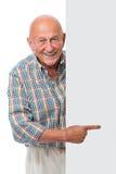 愉快的微笑的老人拿着一个空白董事会 库存图片