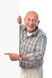 愉快的微笑的老人拿着一个空白董事会 免版税库存照片