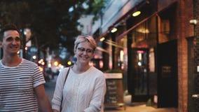 愉快的微笑的西班牙人和白种人妇女举行手、谈话、走沿晚上街道的微笑和亲吻在纽约 股票录像