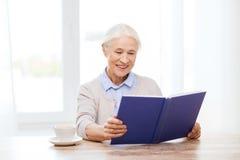 愉快的微笑的资深妇女阅读书在家 库存照片