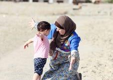 愉快的微笑的阿拉伯回教母亲拥抱她的女婴 免版税库存照片