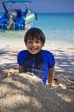 愉快的微笑的年轻人混合了海滩的赛跑的亚裔男孩坐沙子 免版税库存图片