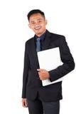愉快的微笑的年轻商人画象,当在他的手上时的膝上型计算机 库存图片