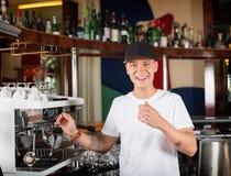 愉快的微笑的barista或侍酒者在咖啡机器旁边 图库摄影