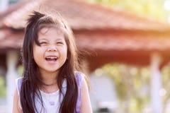 愉快的微笑逗人喜爱小亚裔女孩 免版税库存照片