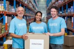 愉快的志愿者是微笑和摆在与捐赠箱子 免版税库存照片
