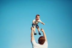愉快的快乐的孩子,父亲乐趣在天空中投掷儿子,夏天 免版税库存图片